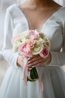 La mariée en robe blanche tient un bouquet de fleurs