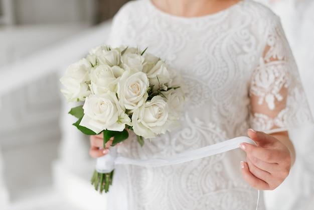 La mariée en robe blanche tient un bouquet de mariée. détails du mariage