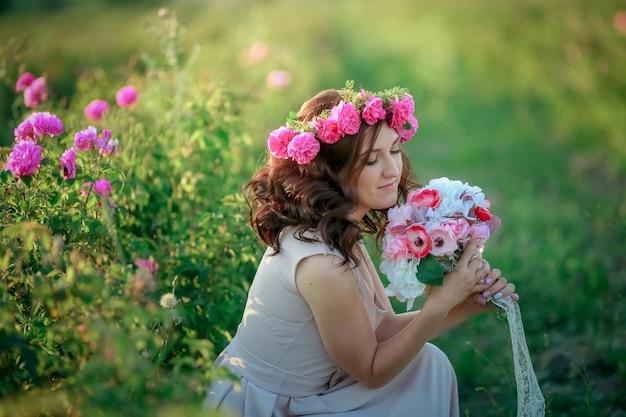 Une mariée en robe blanche tient un bouquet de roses et de callas sur le fond de l'herbe verte.