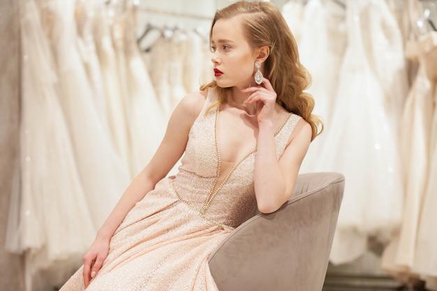 Mariée en robe chic posant sur une chaise dans un salon de mariage