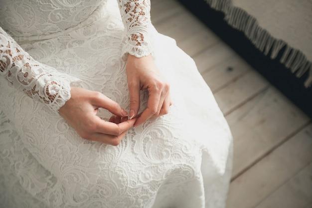 La mariée en robe de mariée blanche et ajourée.