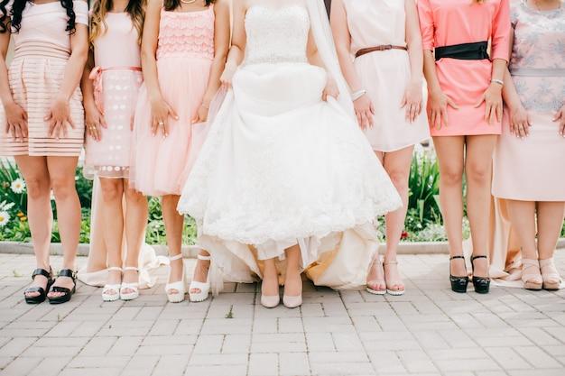 Mariée en robe de mariée blanche debout avec ses amies en plein air.