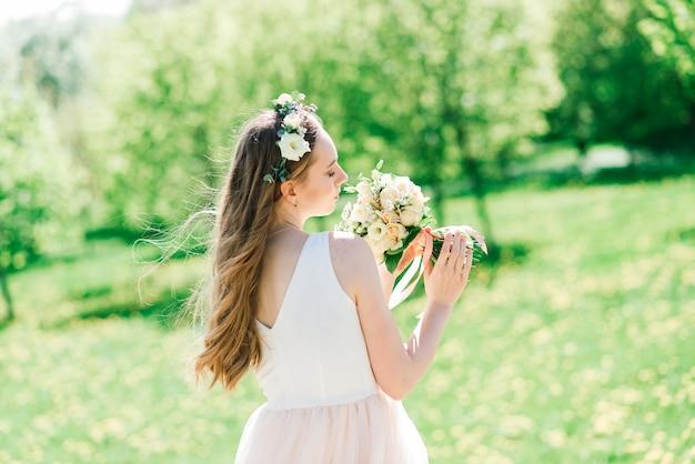 La mariée en robe de mariée blanche tient un bouquet dans le parc verdoyant