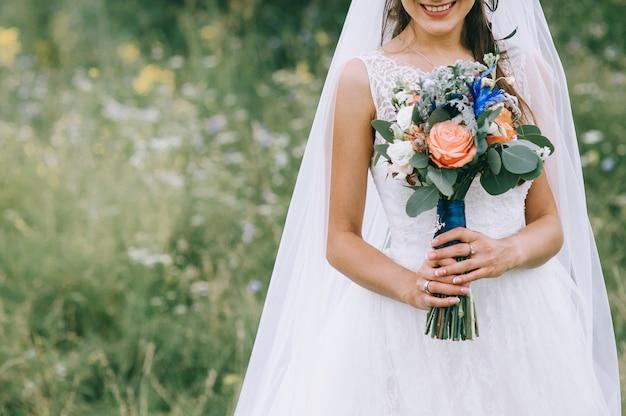 Mariée en robe de mariée avec bouquet de mariée en mains