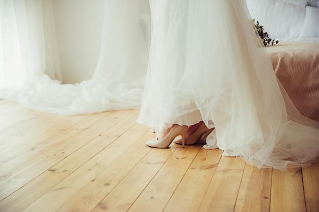 Une mariée en robe de mariée et chaussures sur plancher en bois