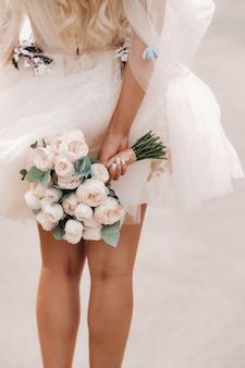 Une mariée avec une robe de mariée courte tient un bouquet derrière son dos