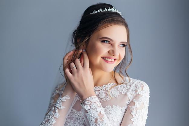 La mariée en robe de mariée fixe la boucle d'oreille