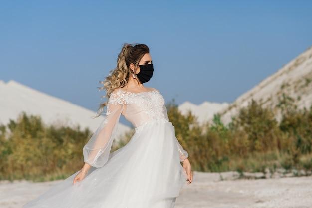 Mariée en robe de mariée avec masque médical en période de quarantaine du coronavirus covid-19.