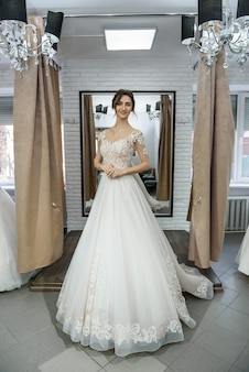 Mariée en robe de mariée posant avec les mains sur la taille