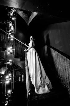 La mariée en robe de mariée se dresse sur un escalier en bois