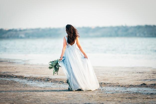 Mariée en robe de mariée se promène au bord de la mer avec bouquet