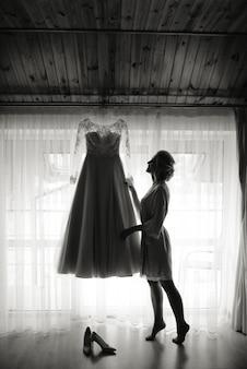 Mariée en robe de nuit tenant sa robe de mariée dans l'ombre