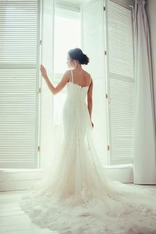 Mariée en robe près de la fenêtre