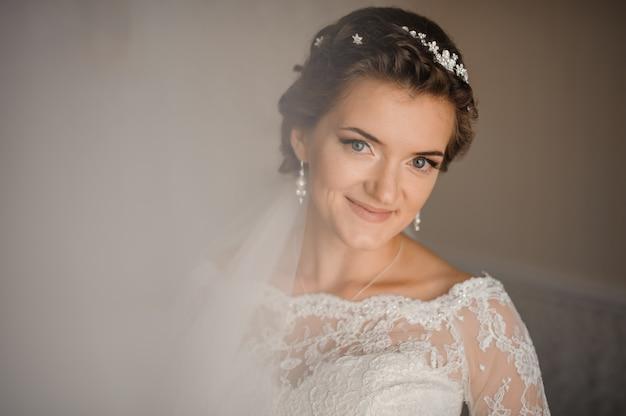 La mariée en robe, le voile et le maquillage sourient doucement
