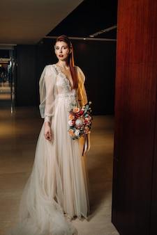 Mariée rousse élégante dans une robe à manches et un bouquet à l'intérieur