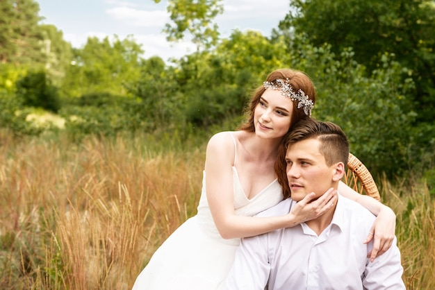Mariée rousse embrasse le marié en forêt