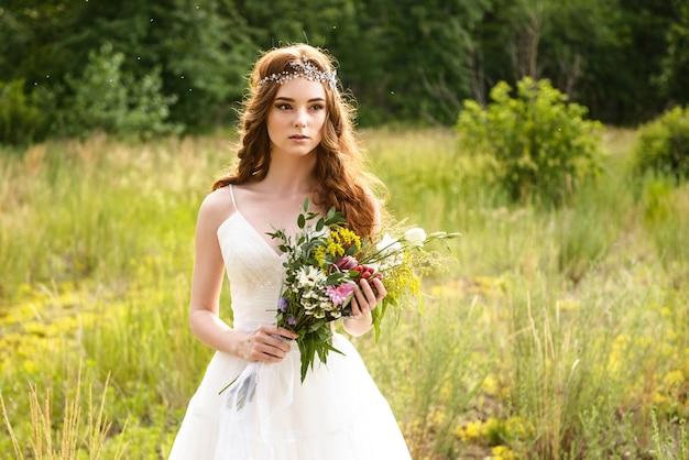 Mariée rousse tenant un bouquet de fleurs de mariage dans ses mains