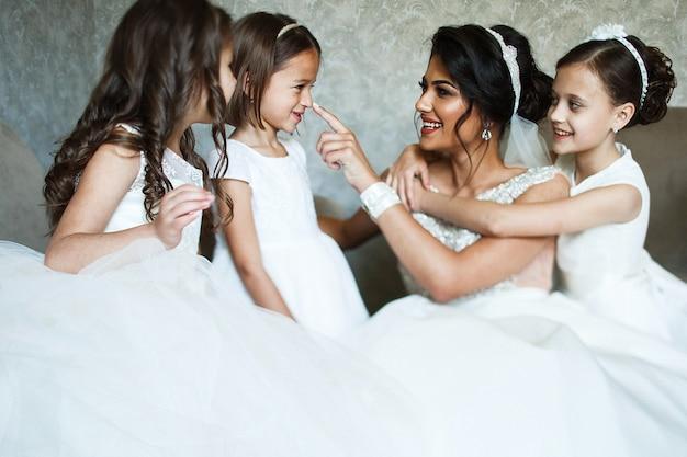 La mariée s'amuse avec de jolies petites filles assises dans la chambre