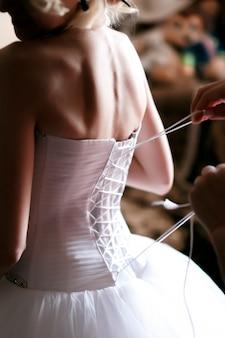 La mariée s'habille dans la pièce.