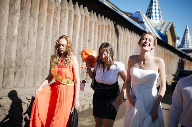 La mariée et sa demoiselle d'honneur marchant avec des amis