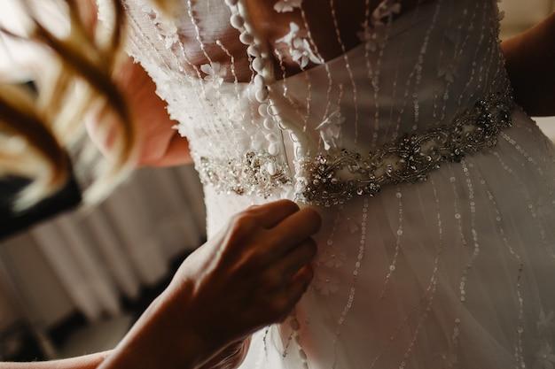 La mariée se préparant, ils l'aident en boutonnant les boutons au dos de sa robe.