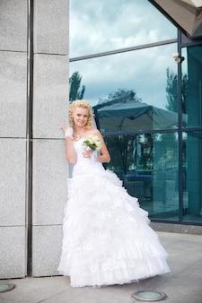 La mariée se tenir à une colonne du bâtiment et de la réflexion dans le verre