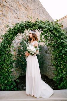 Une mariée se tient à une arche gracieuse enlacée avec des raisins sauvages dans la vieille ville de budva et tient un bouquet dans ses mains