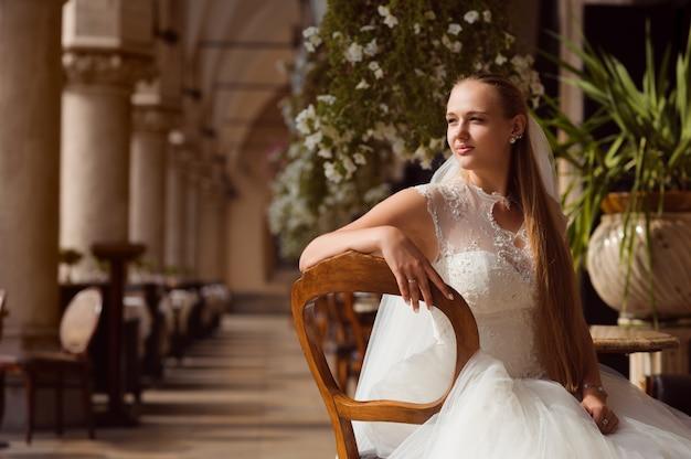 La mariée se tient devant le bâtiment