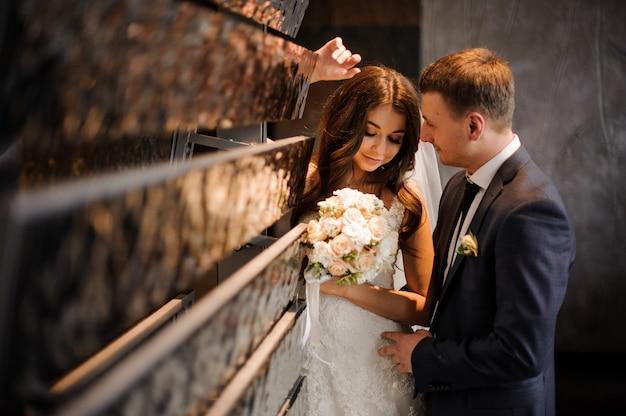La mariée se tient ensemble avec un marié près de l'objet d'art