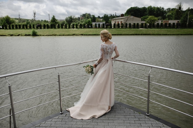 La mariée se tient avec son bouquet de mariée