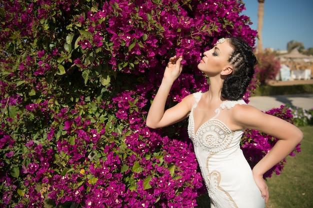 Mariée sensuelle en robe blanche le jour d'été. femme pose avec des fleurs épanouies. mannequin aux cheveux bruns dans le jardin. fille de beauté avec maquillage et look glamour. célébration du mariage et de la fête des femmes