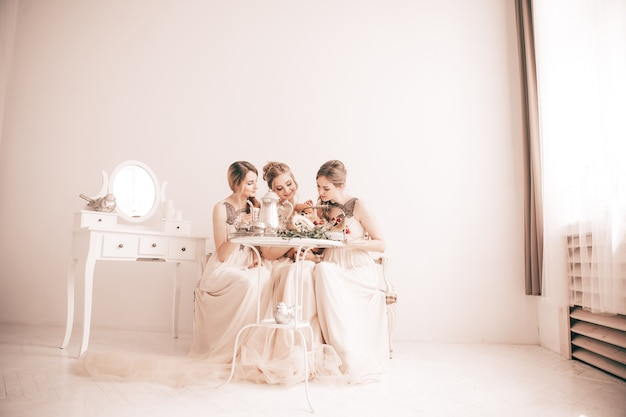 Mariée et ses amis assis à la table de fête dans un boudoir élégant
