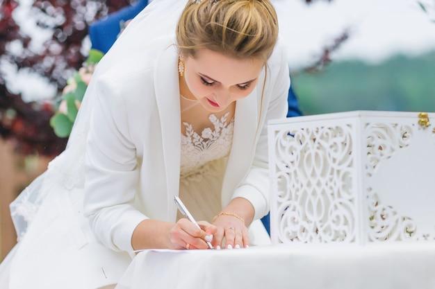 La mariée signe sur le document. cérémonie de mariage. fermer.