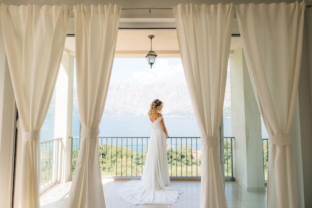 Une mariée sophistiquée dans une élégante robe de mariée se dresse sur un large balcon avec une vue pittoresque