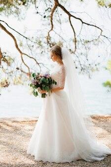 Une mariée sophistiquée se tient avec un bouquet de mariage dans ses mains sous les branches d'un arbre