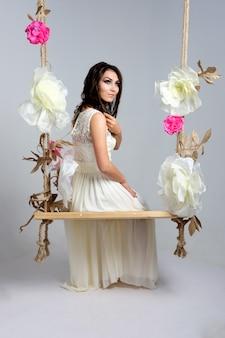 Mariée souriante sur une balançoire en studio. jeune femme brune en robe de mariée