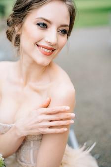 Mariée souriante dans une belle robe a mis sa main sur son portrait d'épaule