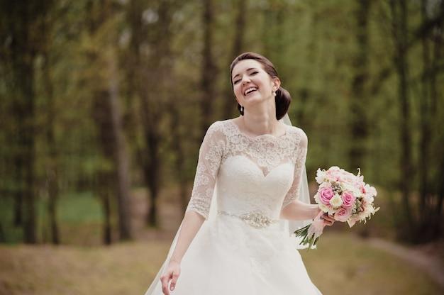 Mariée souriante dans une robe blanche avec un bouquet rose. mariage au printemps