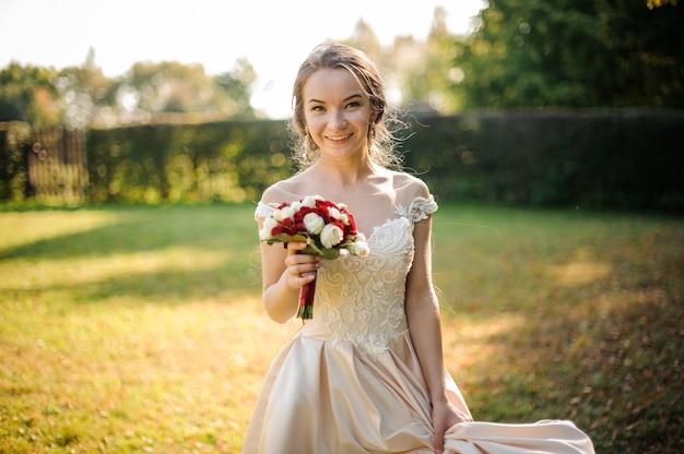Mariée souriante dans une robe blanche tenant un beau bouquet de roses rouges dans le parc verdoyant. conception du mariage