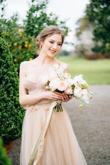 Mariée souriante dans une robe rose avec un bouquet de fleurs sur fond d'arbre vert dans une baignoire