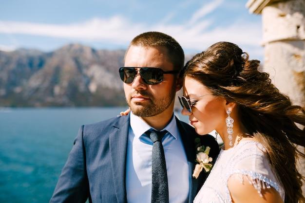La mariée souriante embrasse le marié, ses cheveux flottent dans le vent