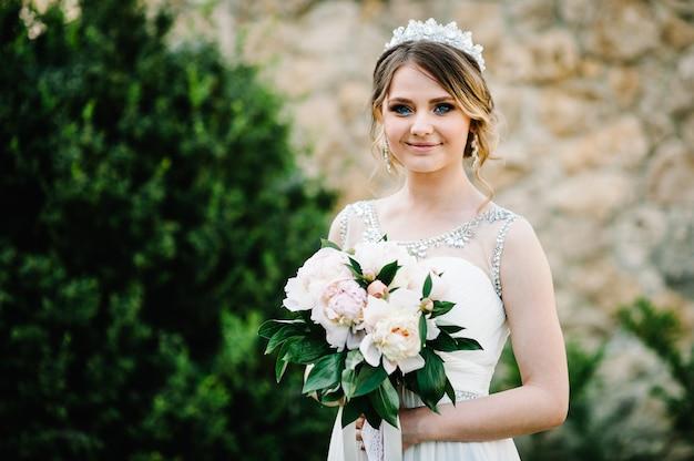 Mariée de sourire élégant avec bouquet de pivoines avec des poses de couronne.