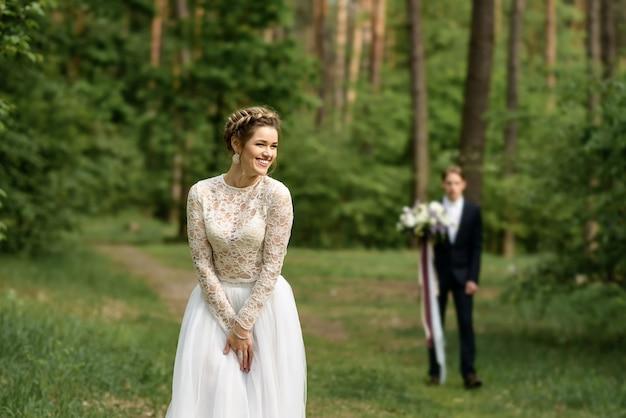 La mariée sourit dans la forêt au premier plan. le marié est flou.