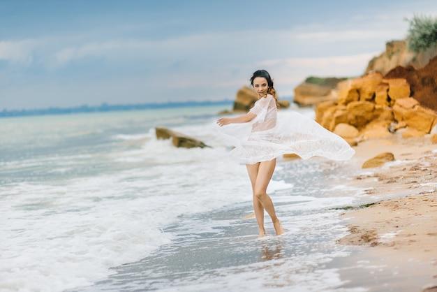 La mariée en sous-vêtements et une robe de chambre avec un voile se promène sur la plage