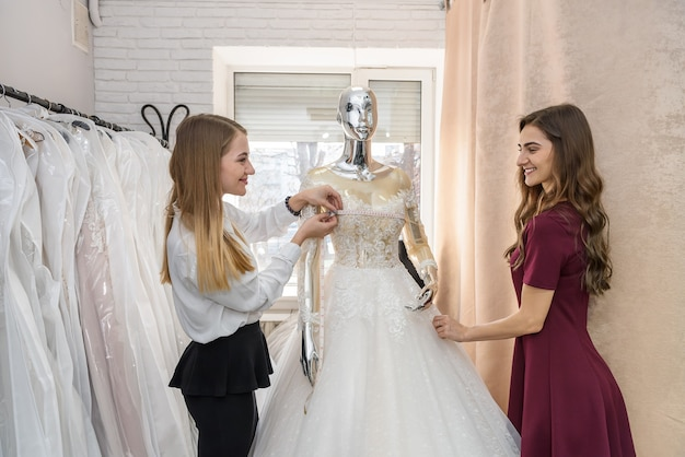 Mariée avec tailleur en choisissant la robe de mariée en magasin