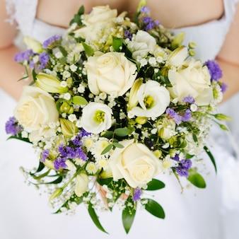 Mariée tenant beau bouquet de fleurs de mariage