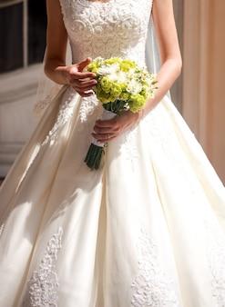 Mariée tenant beau bouquet de mariage de fleurs au soleil