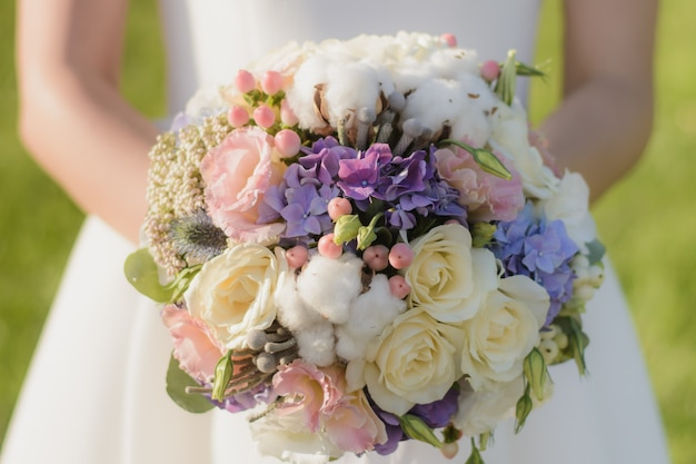 Mariée tenant beau bouquet de mariée en mains