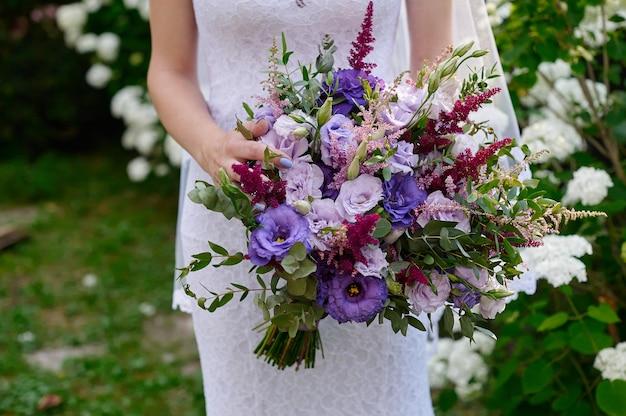 Mariée tenant un beau bouquet de mariée sur la promenade.