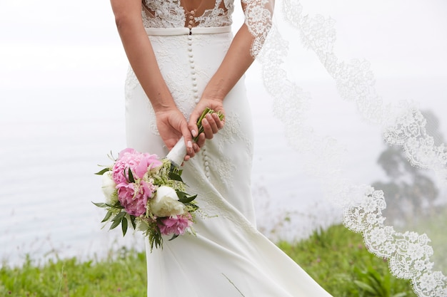 Mariée tenant un bouquet de fleurs au bord de la mer